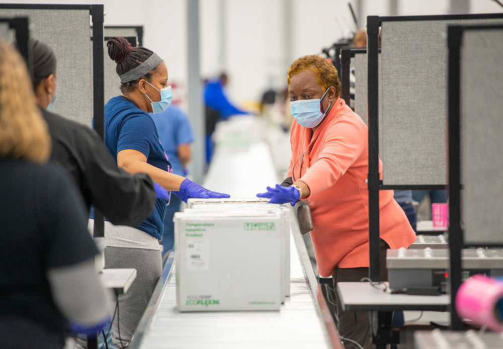 Distribution center employees inspect packages ready for shipping