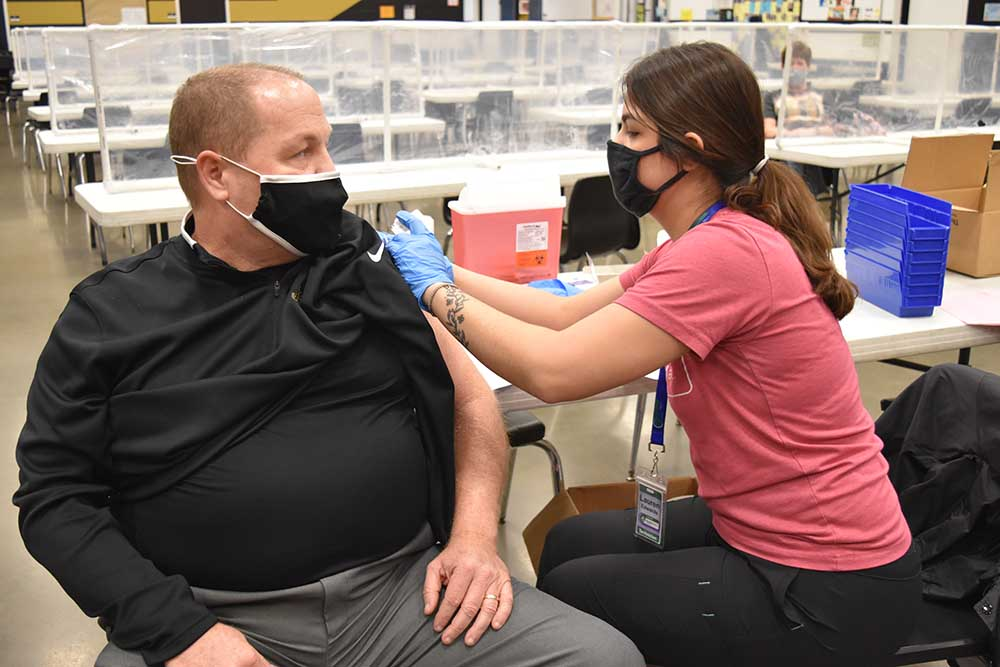 Craig Gibbs, principal of Fredericktown High School in Missouri, receiving his COVID-19 vaccine from Lauryn Edwards, a Parkland Health Mart Pharmacy team member on March 18, 2021.