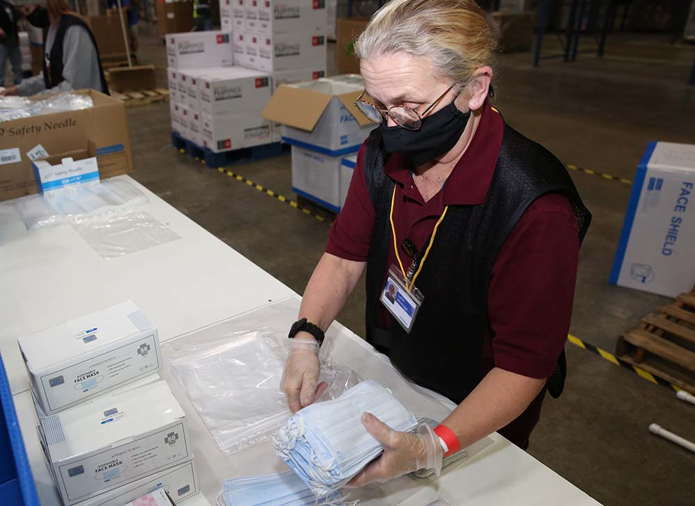 A worker assembles the contents of a COVID-19 vaccine ancillary supply kit at McKesson's Manteno, IL distribution center.