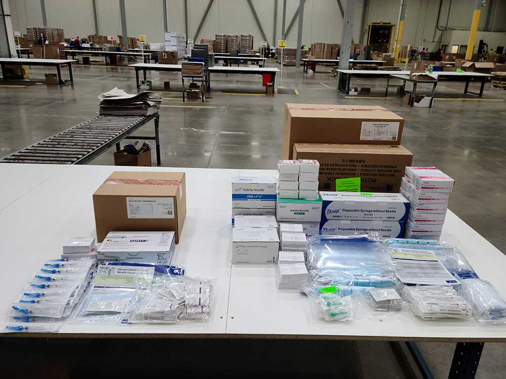 Displayed on the table above are ancillary supply kits for Moderna's vaccine (left) and for Pfizer's (right).