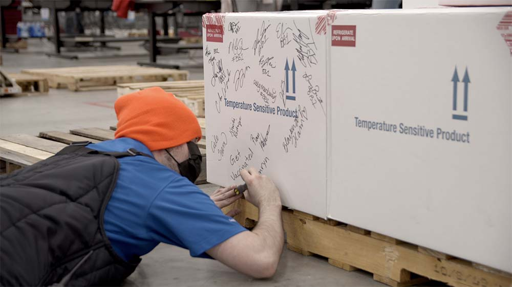 Workers at McKesson's Louisville, Ky. distribution center sign the first box of Janssen's COVID-19 vaccines from Johnson & Johnson.