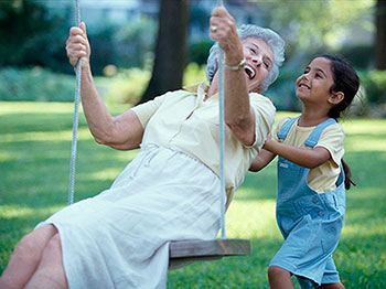 grandmother on swing with granddaughter pushing
