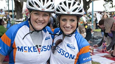 Two female employees with McKesson bike jerseys on, arms around each other after a bike race.